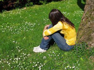 girl sitting against a tree alone on the grass