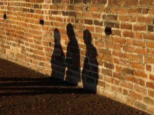 shadows of 3 people on a wall
