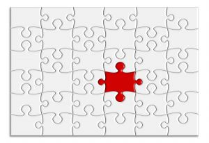 white jigsaw with one red piece