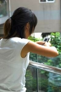 woman leaning over a balcony texting