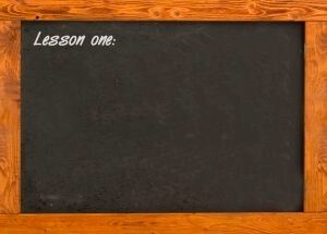 lesson one written in chalk on a blackboard