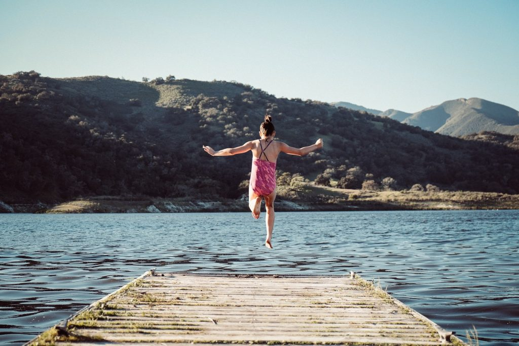 woman jumping into the water, the uknown. Ready to move on. Photo by Erik Dungan on Unsplash