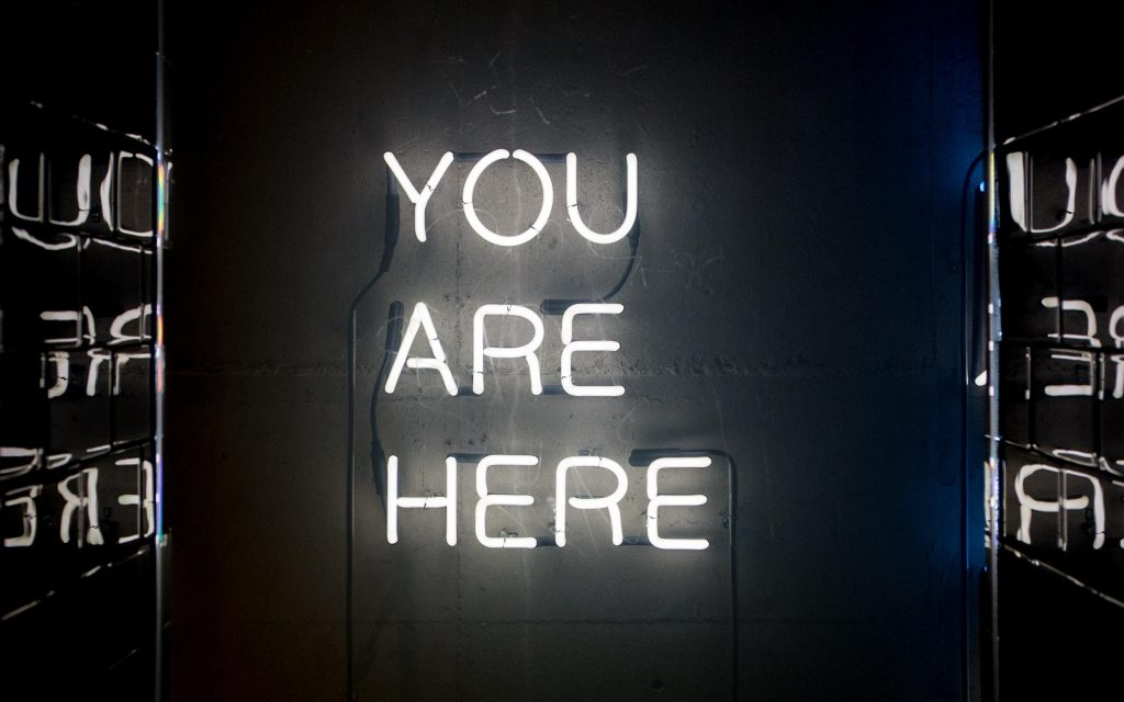 'you are here' in lights Photo by John Baker on Unsplash